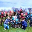 Groep jongeren in paintball outfit met jongerenwerkers