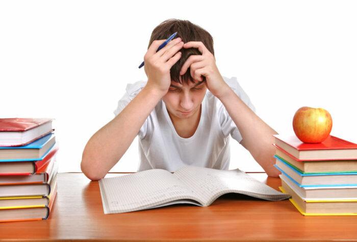 Jongen achter stapel leerboeken met handen in het haar