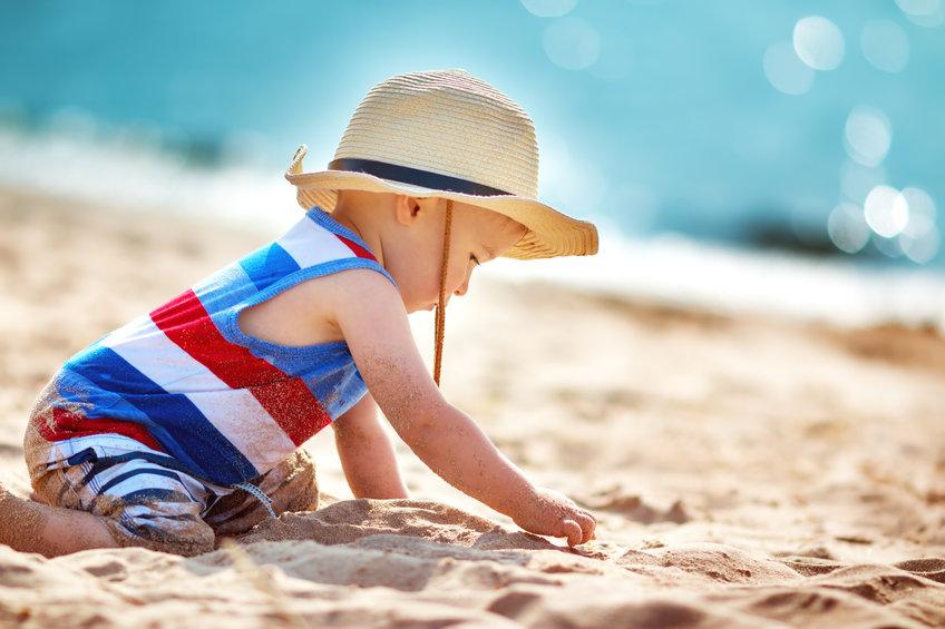 Baby met zonnehoed op het strand