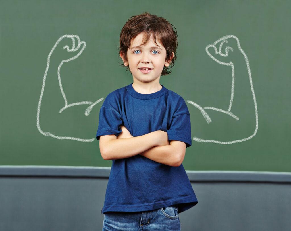 Sterk jongetje met de armen over elkaarvoor schoolbord