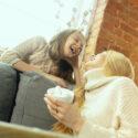 Moeder en dochter in gesprek met koffie in de hand