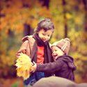Kleine kinderen spelen met herfstbladeren in het bos